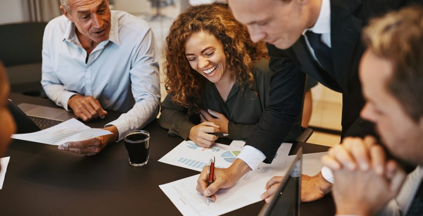 Smiling businesspeople going over paperwork together during an office meeting